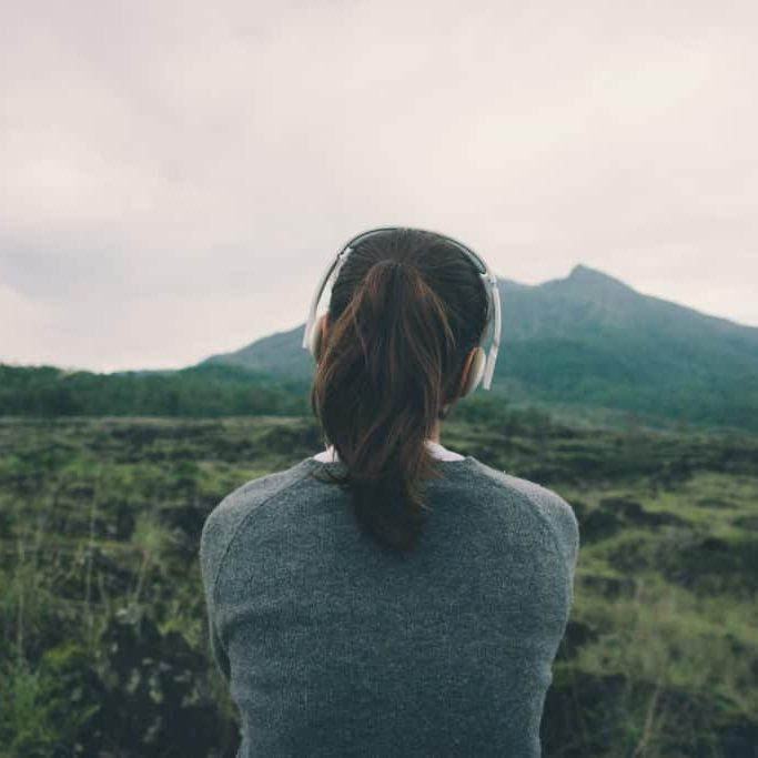 Woman in headphones listening music in nature and at the mountain (intentional pale color style)
